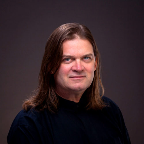 Rev. Scott Sammler-Michael in a headshot wearing a black button up shirt. His straight brown hair falls just past his shoulders.